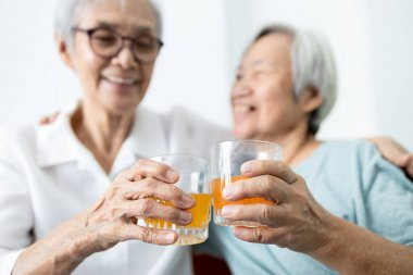 Healthy elderly sibling drinking vitamin C,orange juice and clinking glasses at home,senior people with effervescent vitamin C,strengthening the immunity for cold,flu,prevent the Covid-19,health care
