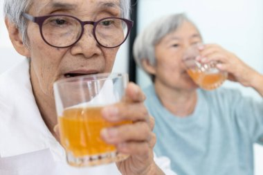 Healthy asian elderly sibling are drinking glasses of vitamin C,orange juice,senior people with effervescent vitamin C,strengthening the immunity for cold,influenza,prevent the Coronavirus,stay home