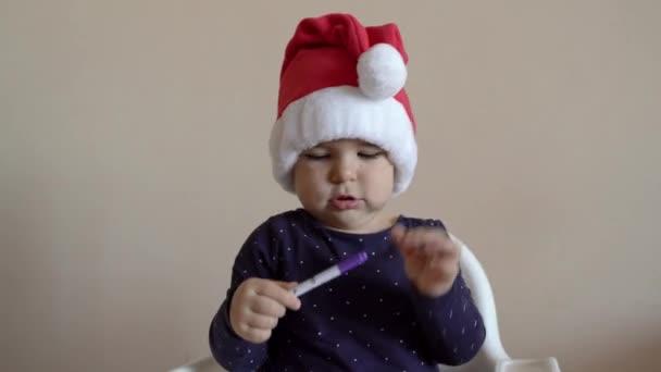 Dítě v Santově klobouku si hraje s plstěnými pery. Zbarvení knihy. Kreativní aktivita. Indoors celebrating
