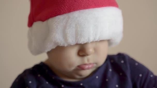 Nahaufnahme Baby-Porträt mit Weihnachtsmann-roter Mütze. Ernsthafter Gesichtsausdruck. Lustiges Kind