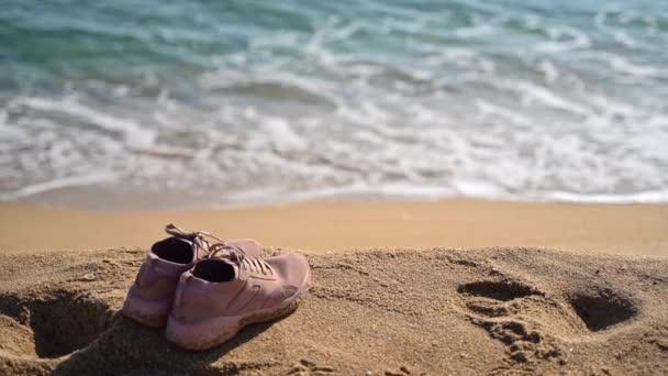 Cestování nebo jogging na pláži koncept. Sportovní boty na pobřeží. Zpomalený pohyb