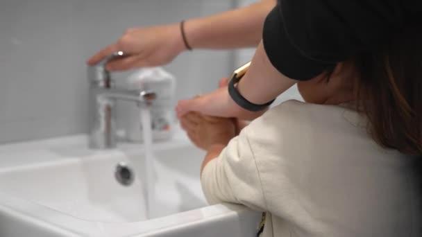 Fiatal anya gyermek mosás kezet otthon antibakteriális szappannal
