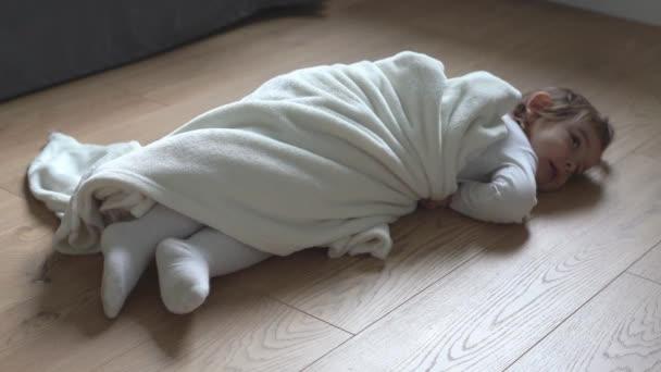 Fiatal csecsemő feküdt a padlón fehér takaróval. Fáradt gyermek