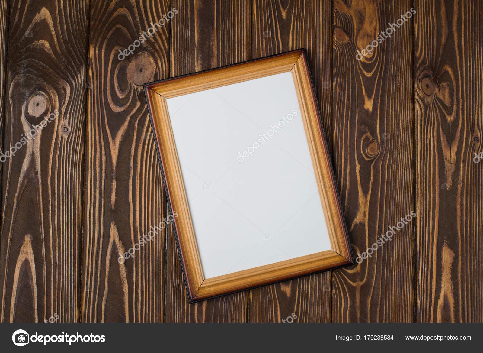 Marco de madera oscura con un cuadro vacío, sobre un fondo oscuro ...