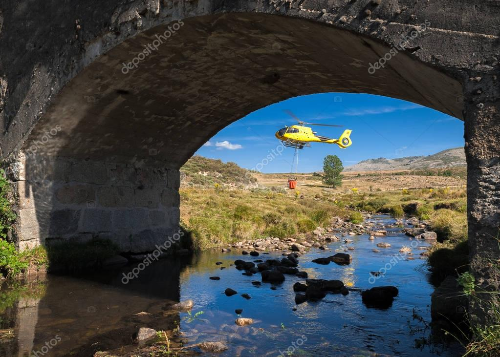 Helicopter firefighters picking up water from small river