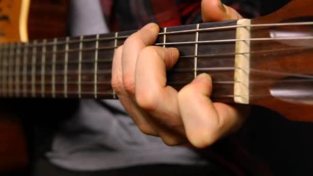 Kytaristé levou rukou hrají akordy.