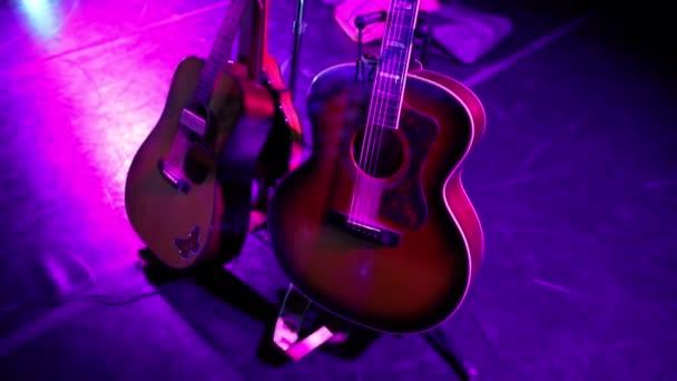 Akustické kytary a mandolína na stojanech