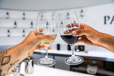 red and white wine glasses cheering