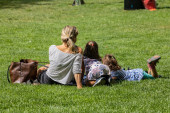 Family sitting on grassy lawn in park