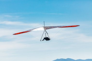 Hang gliding over valley farmlands and mountains