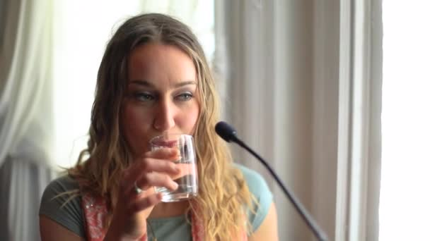 Woman drinking water during interview