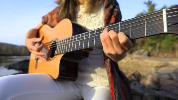Kytarista žena hraje na akustickou kytaru