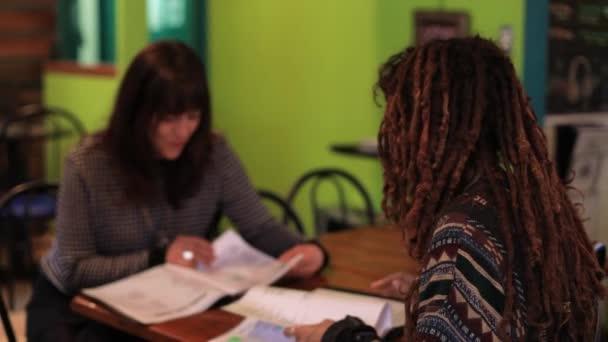 Barátok beszélgetnek miközben kaját rendelnek a kávézóban.