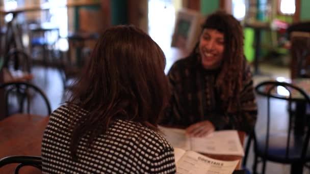 Barátok pletykálnak, miközben kaját rendelnek a kávézóban.