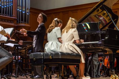 2020.02.15, Moscow, Russia. reporting concert of the orchestra and soloists of secondary and senior students of the music school named after Alekseev. Two girls playing four hands concert.