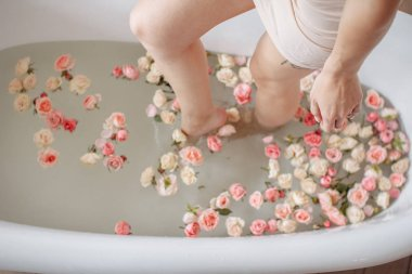 Woman relaxing in round outdoor bath with tropical flowers, organic skin care, luxury spa hotel, lifestyle photo.