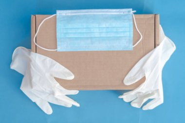 different medical gloves with cardboard box, concept of mail goods delivery in virus quarantine, banner with copy space on blue background