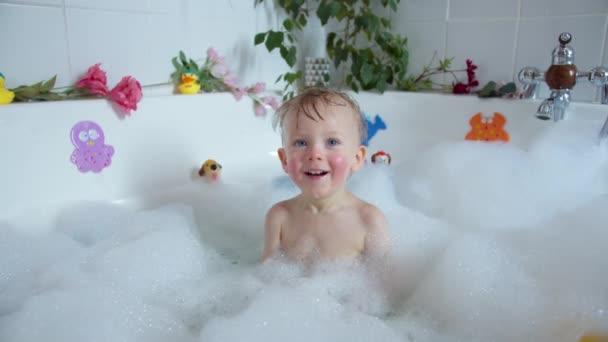 Kleines Kind im mit Schaum gefüllten Bad, spielt mit Spielzeug und lächelt, Mütter Hände seifen Babys Kopf mit Baby-Shampoo