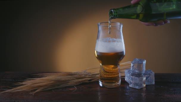 zblízka mužská ruka nalévá pivo do sklenice, ječmen a led leží na stole