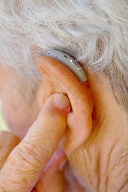 senior woman inserting hearing aid in her ears