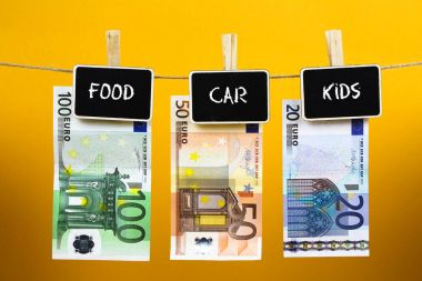 Bank notes suspended with pins with Words - Food Car kids - written on a slate