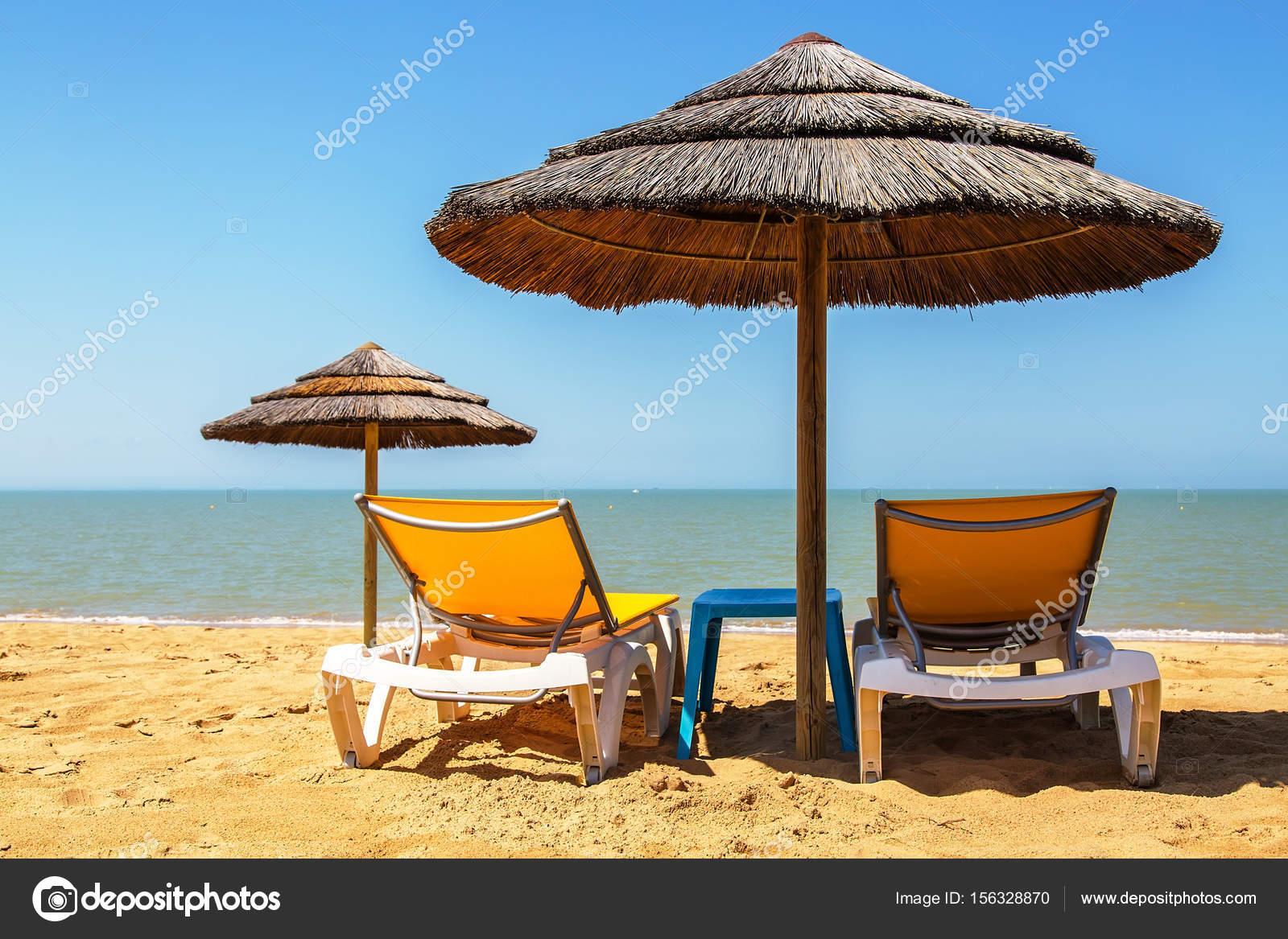 Liegestuhl mit sonnenschirm strand  Sonnenschirm und Liegestuhl am tropischen Strand — Stockfoto ...