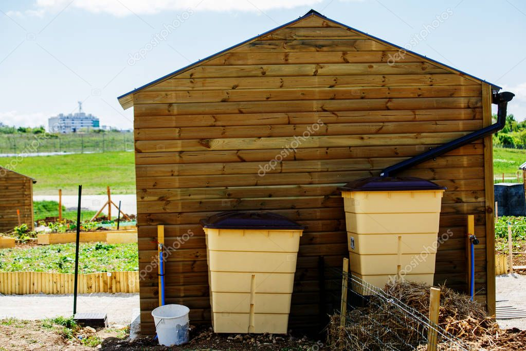 Green recovery of rainwater and small wooden cabin outside in to