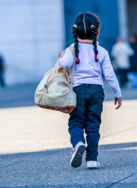 La defense, France - April 9, 2014: Rear view of child walking on city road