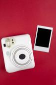 Moderní polaroidní kamera, červené pozadí. Horní pohled, jemné minimální plochý styl ležel kompozice. módní blogger, krása technologie