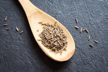 Cumin seeds. Close up image of cumin (zira) seeds on rustic wooden spoon and black background.