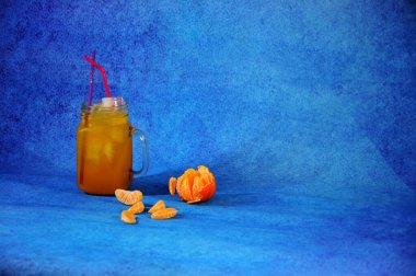 Glass mug of citrus juice with ice with slices of mandarin on a blue background. Close-up.