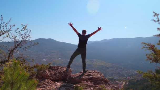 A fiatal ihletett férfi felemeli a kezét egy hegy tetején állva.