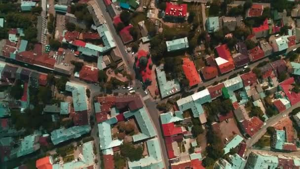 Aerial footage of streets, blocks and house roofs in the cityscape on a sunny summer day with camera rotating.