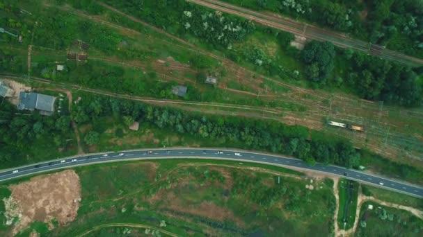 Pohled z ptačí perspektivy na krajinu s dálniční dopravou a železničními tratěmi na boku.