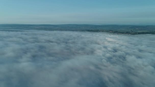 Forward movement of an aereal view with a big settlements on the hills covered with fog on sunrise.