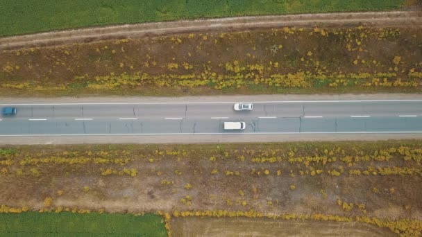 Letecký pohled nad vozy jedoucí na vysoké rychlosti podél venkovské silnice na slunný den.