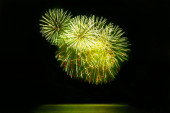 Beautiful fireworks display on evening black sky. In green and golden color holiday background with copy space for text
