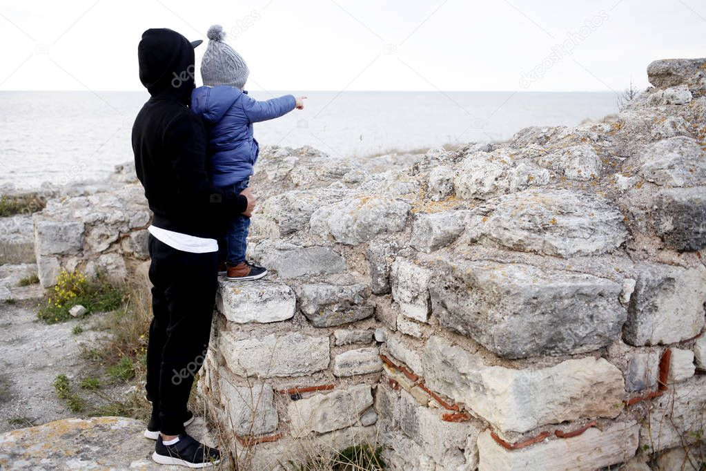father with little boy standing in ruins