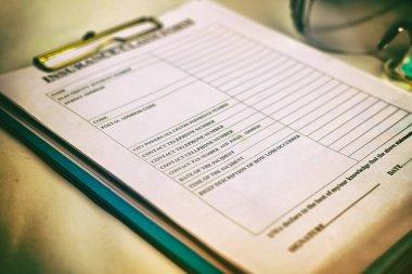 Blurred of insurance claim form put on desk,dramatic tone,blurry light around