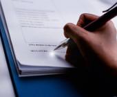 Stift wurde von verschwommener menschlicher Hand gehalten und Signatur blank, Linsenschlageffekt, verschwommenes Licht