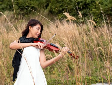 The beautiful woman playing violin with happy feeling, in a park