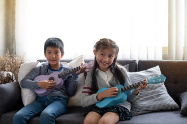 Two children playing ukulele togetherwith smile and happy feeling,at studio,blurry lightaround