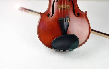 Front side of violin put in front of blurred bow,on background