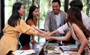 Young business people stacked hand together ,after finish working ,with colleagues team meeting,success deal,with happy feeling
