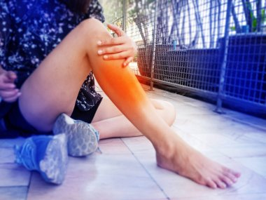 In selective focus of lady leg was touch by hand ,with orange circle around.The .Shin splints symptom, soreness or pain along the inner side of your shinbone and mild swelling in your lower leg,while exercise,blurry light around