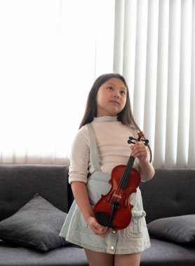 The little girl holding violin in hand,turn face up looking straight,at home studio.blurry light around