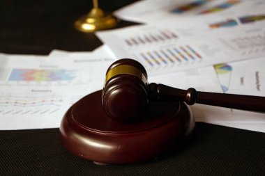 Closeup wooden judge gavel put in front of blurred business paper chart,blurry light design background