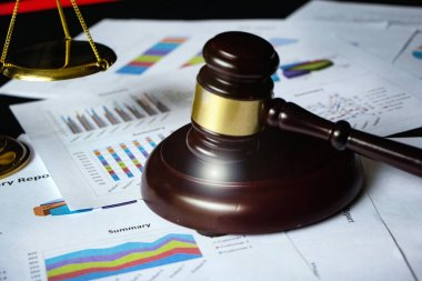 Blurred of wooden judge gavel put on business paper chart,Lens flare effect