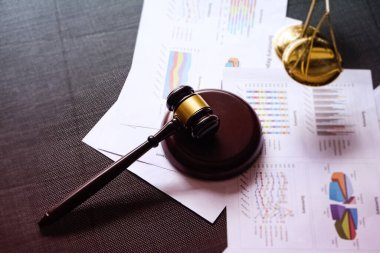 The wooden judge gavel put on blurred business paper chart