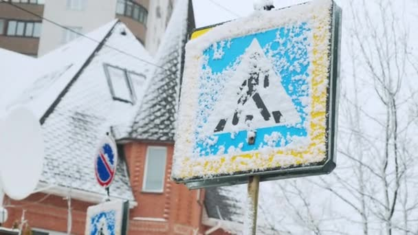 Allowed pedestrian crossing. Road sign blue color of the pointer of crosswalk and direction of travel. Snowy winter trees. Snowfall, winter after heavy snow, after a storm, cloudy gray sky